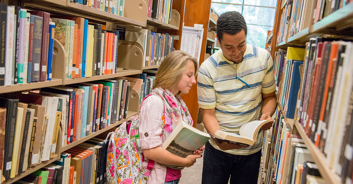 Two students looking at books in the library