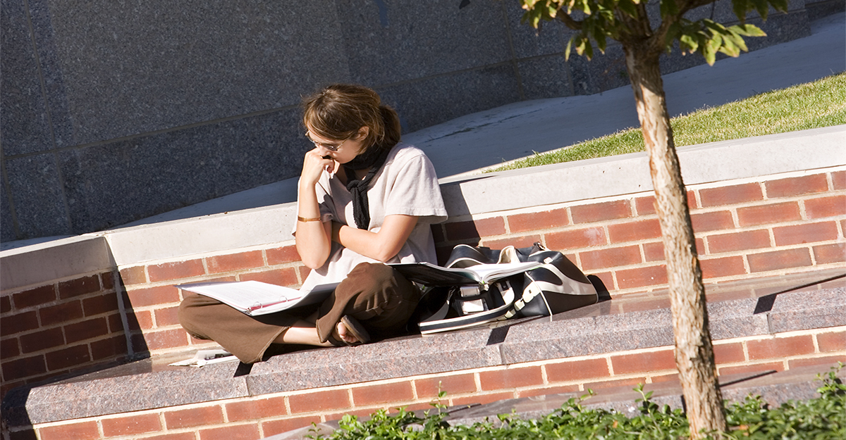 Student reading textbook while seated outdoors