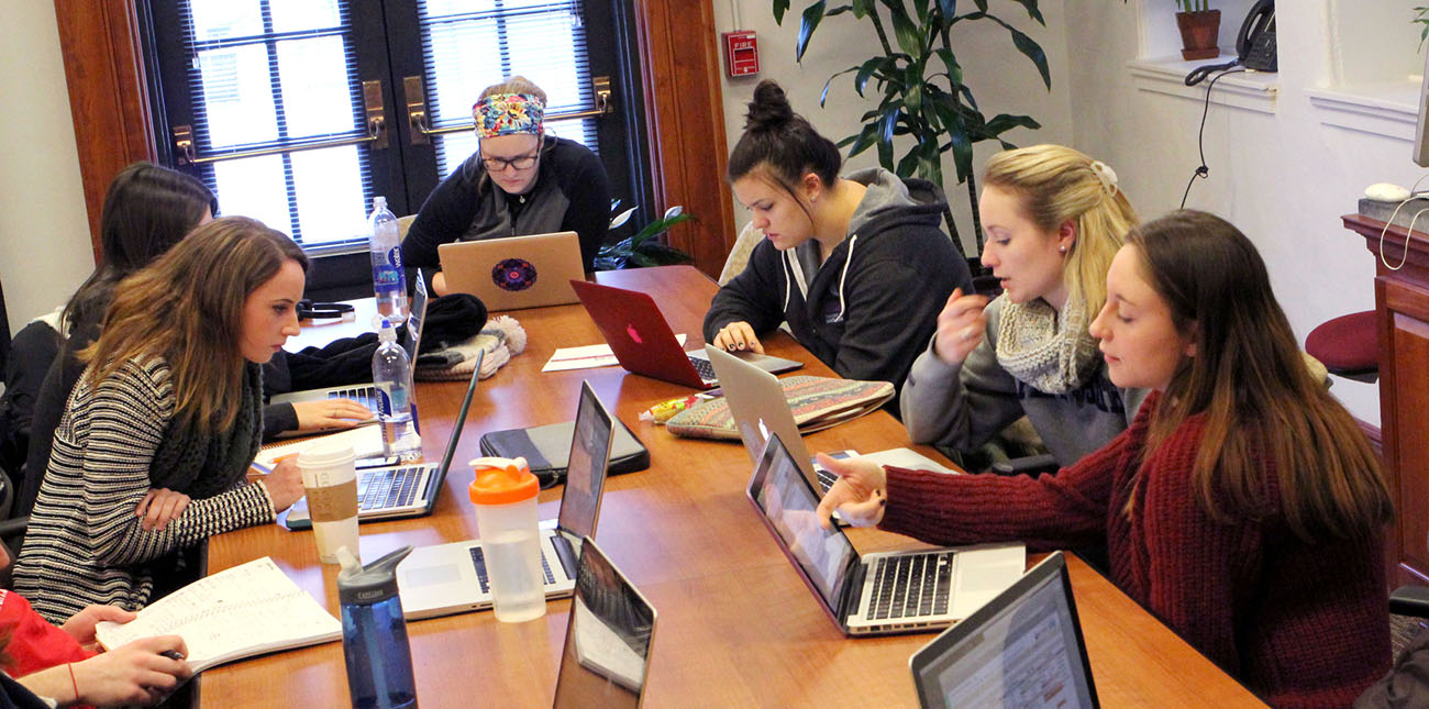 Students using laptops to review work during group project