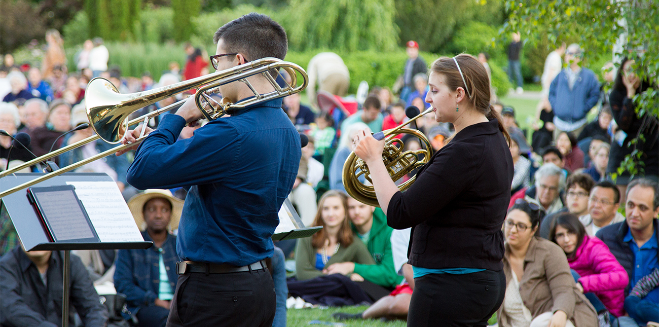 Students playing trombone and French horn at the Arboretum
