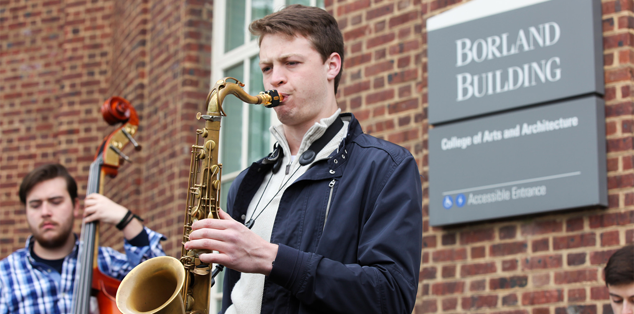 Music student playing saxophone with jazz combo