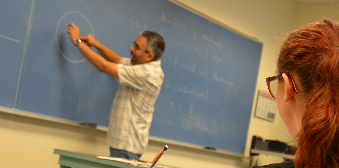 Student watching math professor draw circle on chalkboard in class