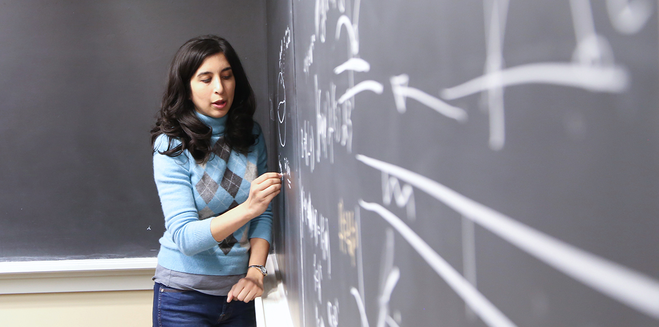 Student completing a math problem on a chalkboard