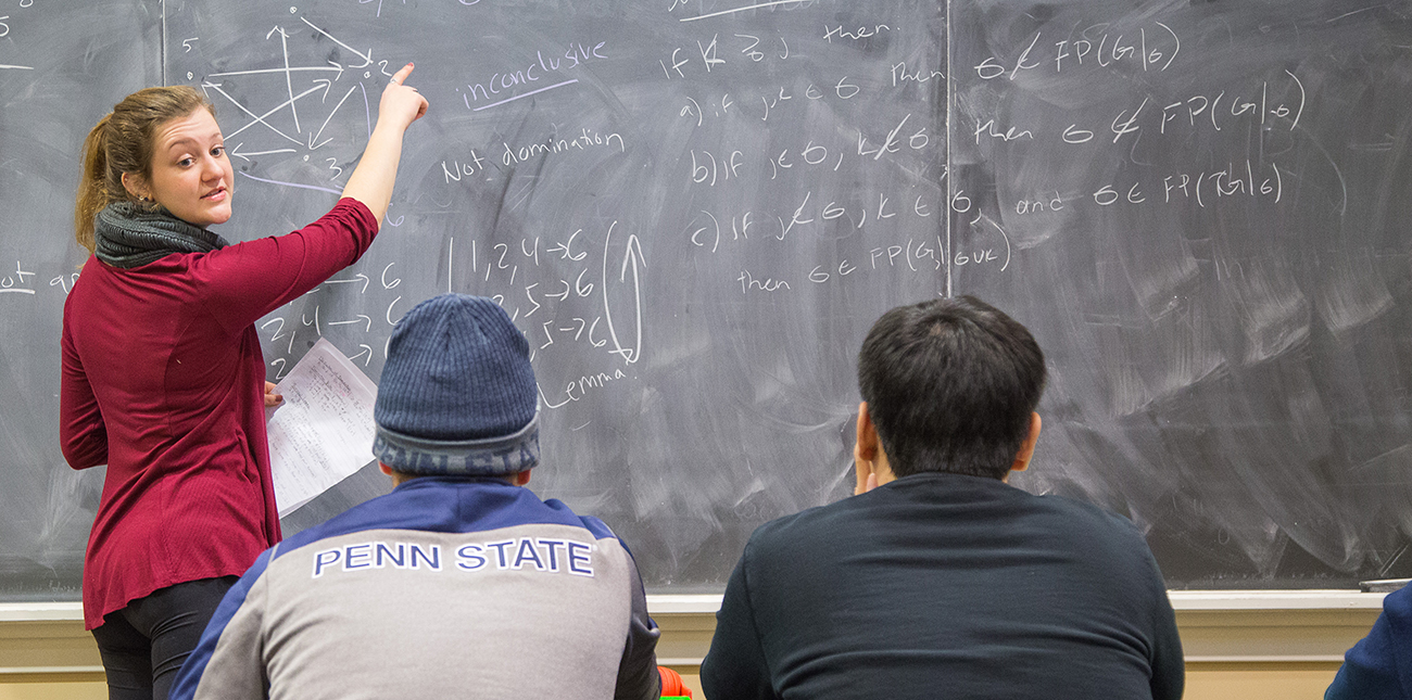 Instructor and students in a mathematics class with equations on the chalkboard