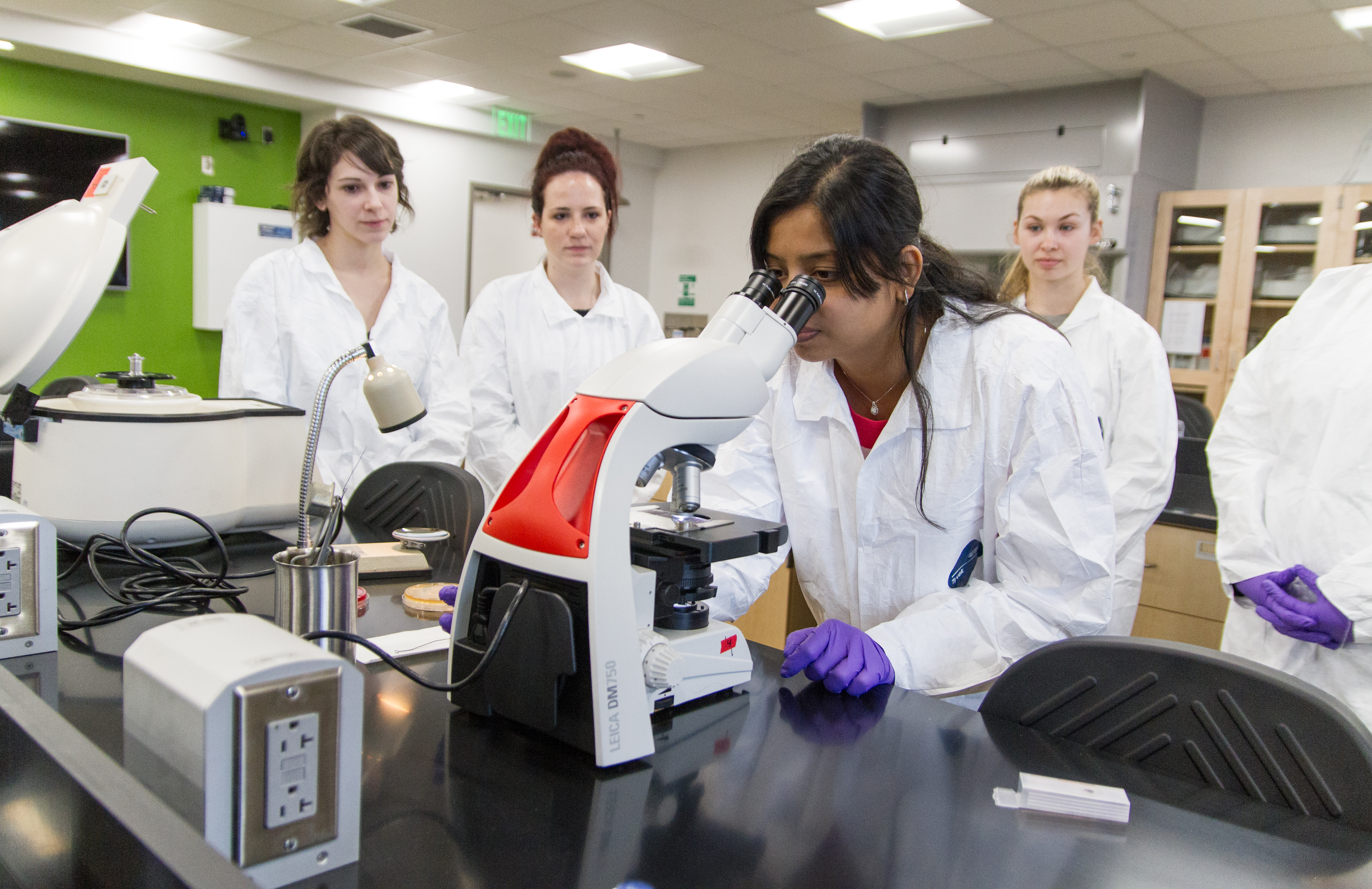 Student in a lab examining a specimen under a microscope surrounded by several students