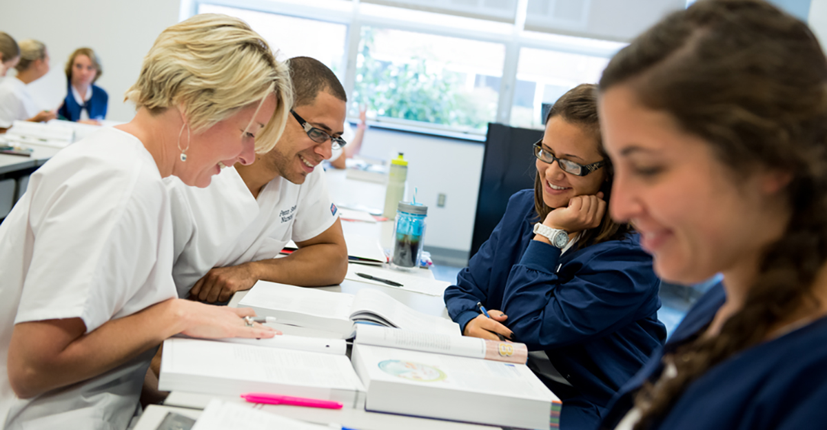 Four nursing students review textbooks together at a classroom table.
