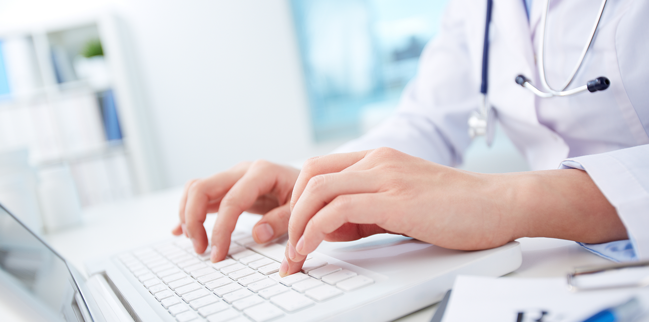Close up of nurse typing on a laptop