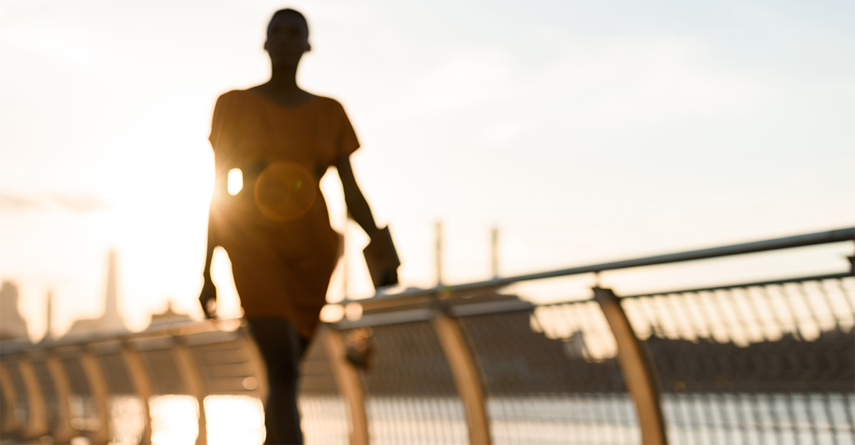 Silhouette of business woman walking at sun set