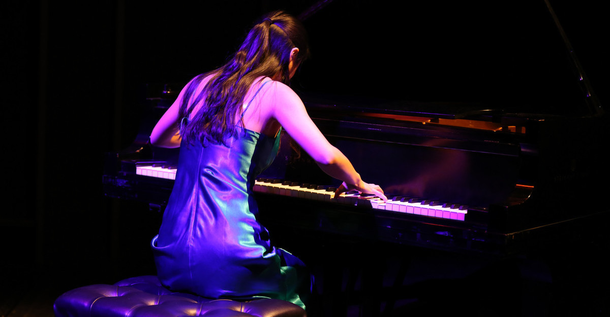This photo shows a woman playing the piano.
