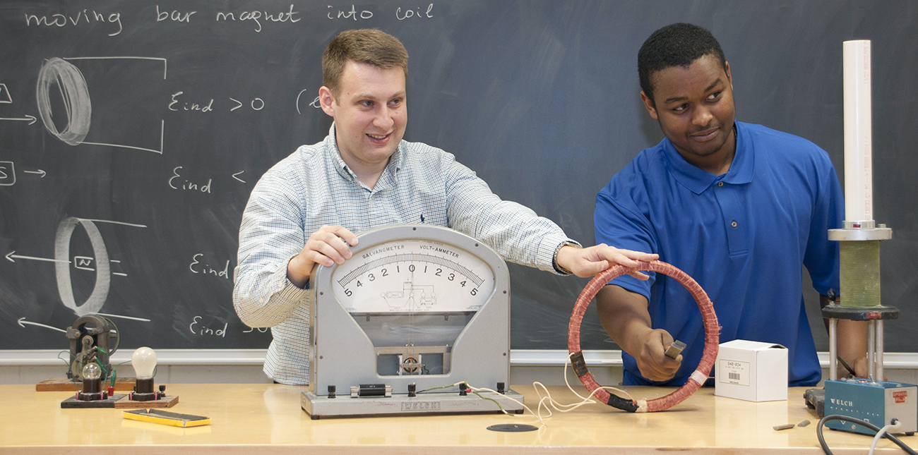 Faculty member and student perform physics demonstration in class