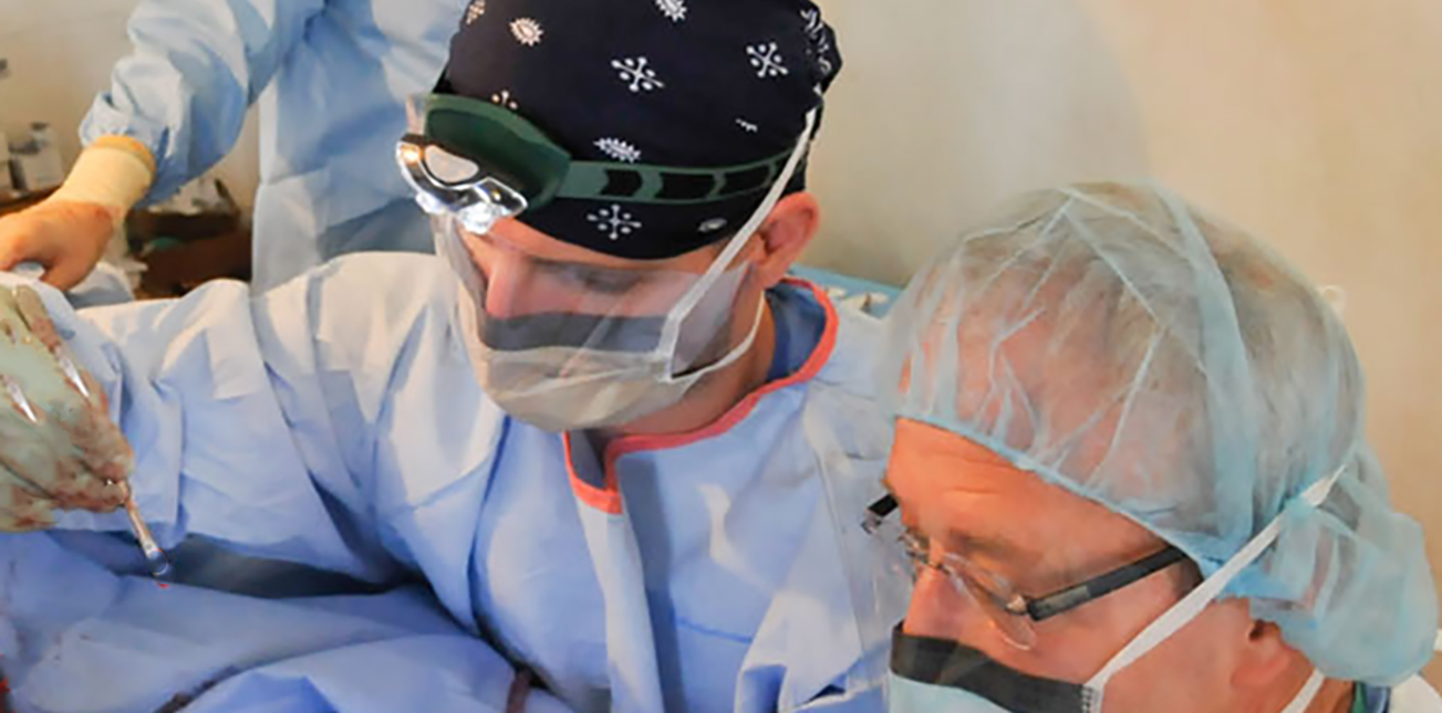 Student assisting doctor in surgery