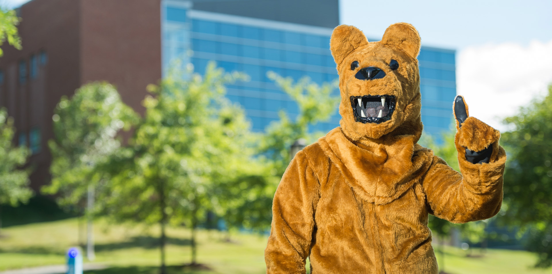 "The Nittany Lion mascot making a ""we're number one"" gesture in front of Burke Center"