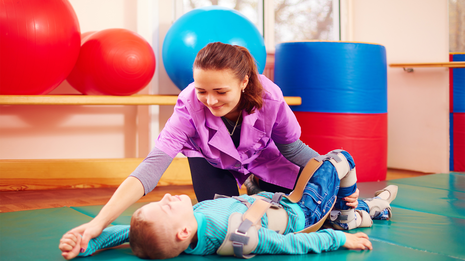 Individual working with child in rehabilitation center