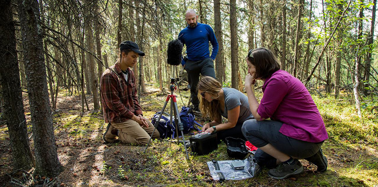 Students and faculty member outside setting up a microphone on a tripod