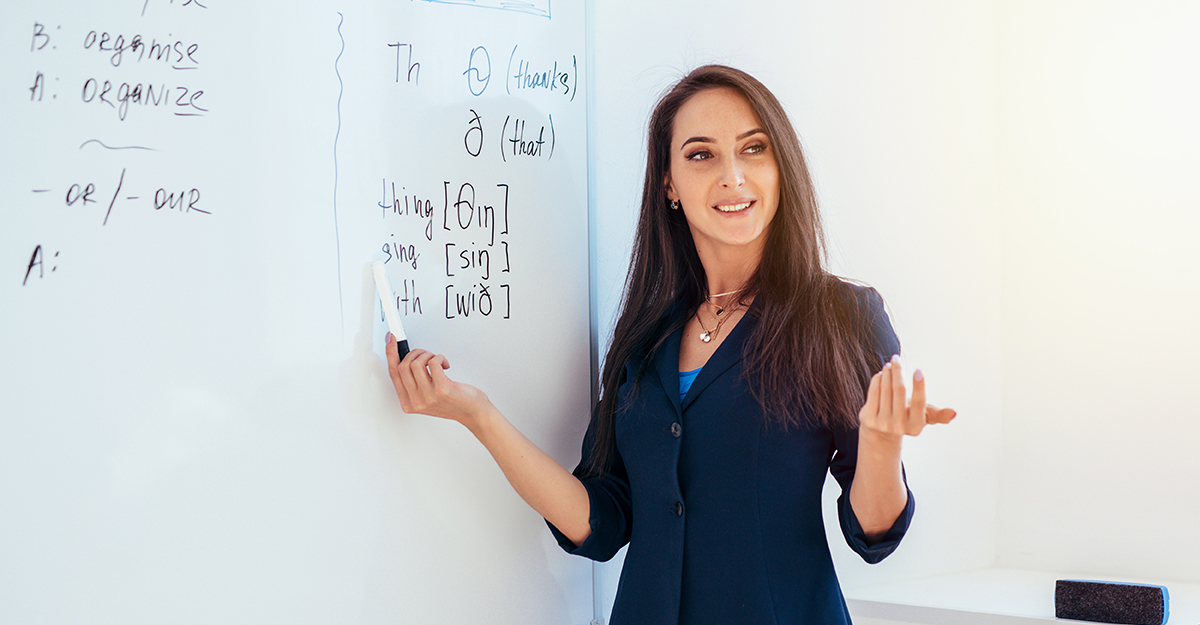 Teacher stands in front of whiteboard while presenting English language topics