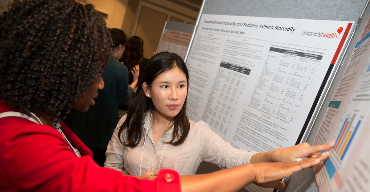 Sociology graduate student presents her research on Korean families at a poster exhibition to a faculty member.