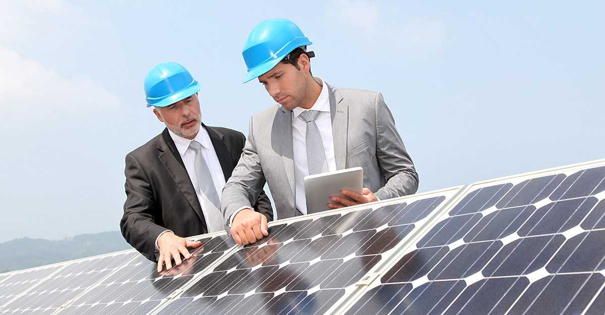Two people working on solar panels.