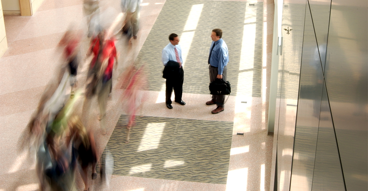 Two business professionals standing in a hallway with passersby blurred