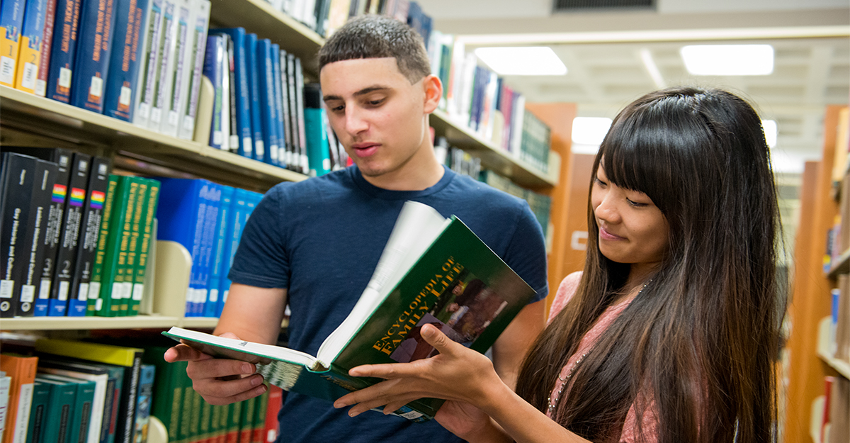 Two students looking at family life textbook in the library