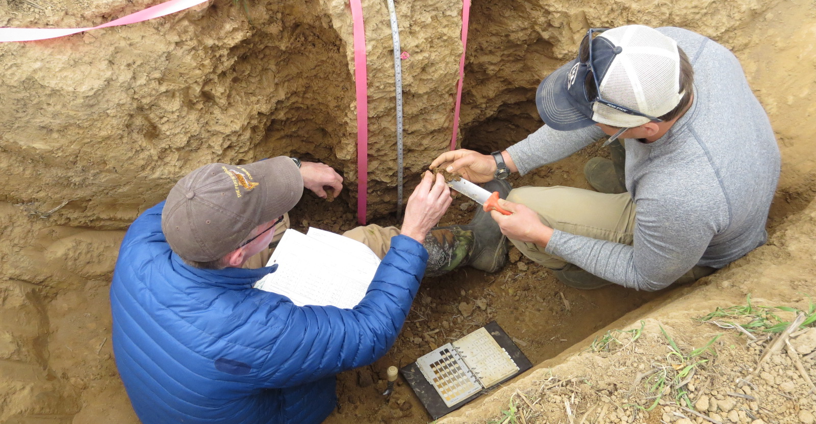 Two soil scientists in a soil pit