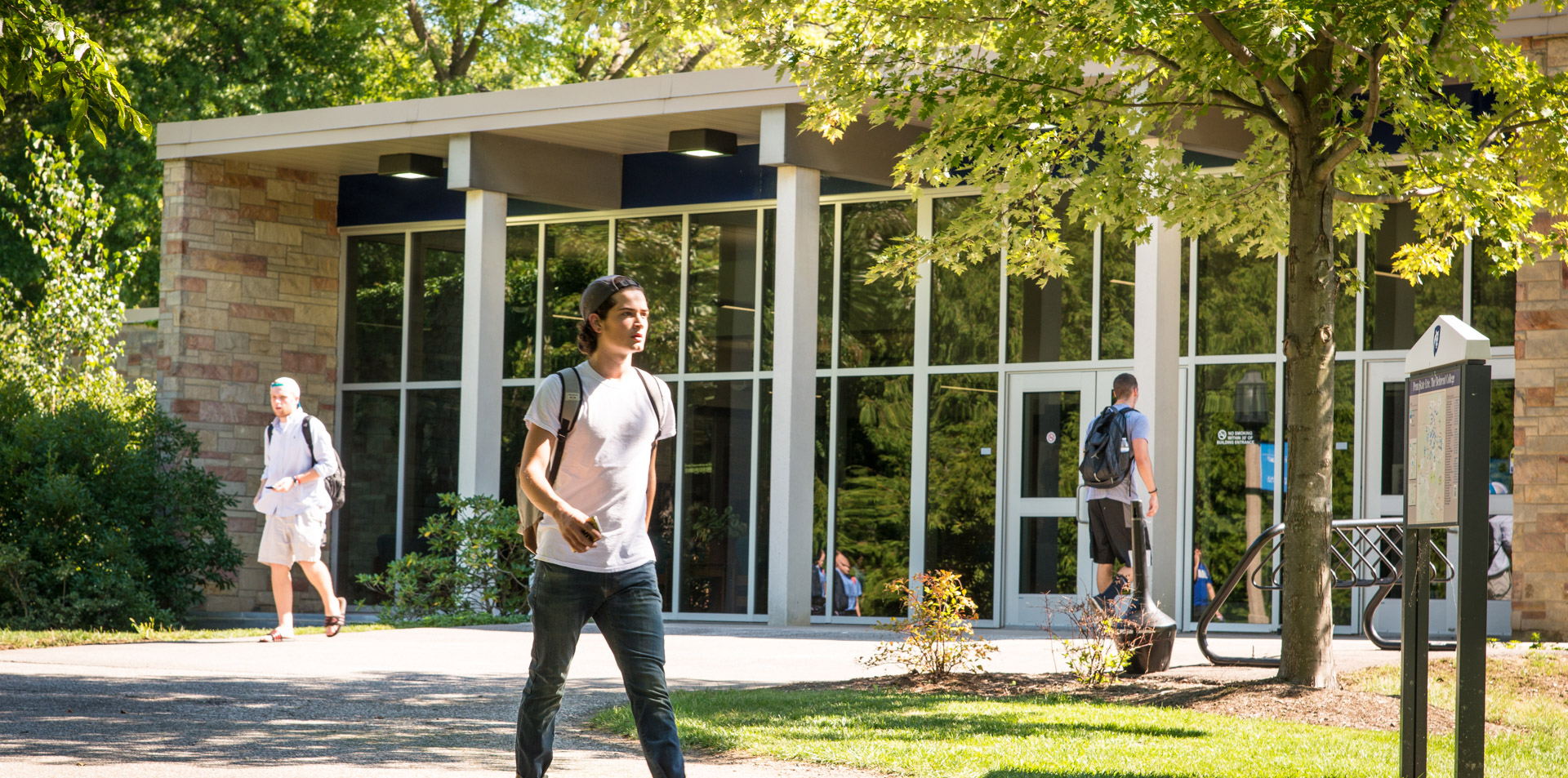 Student walking in front of the Otto Behrend Science Building