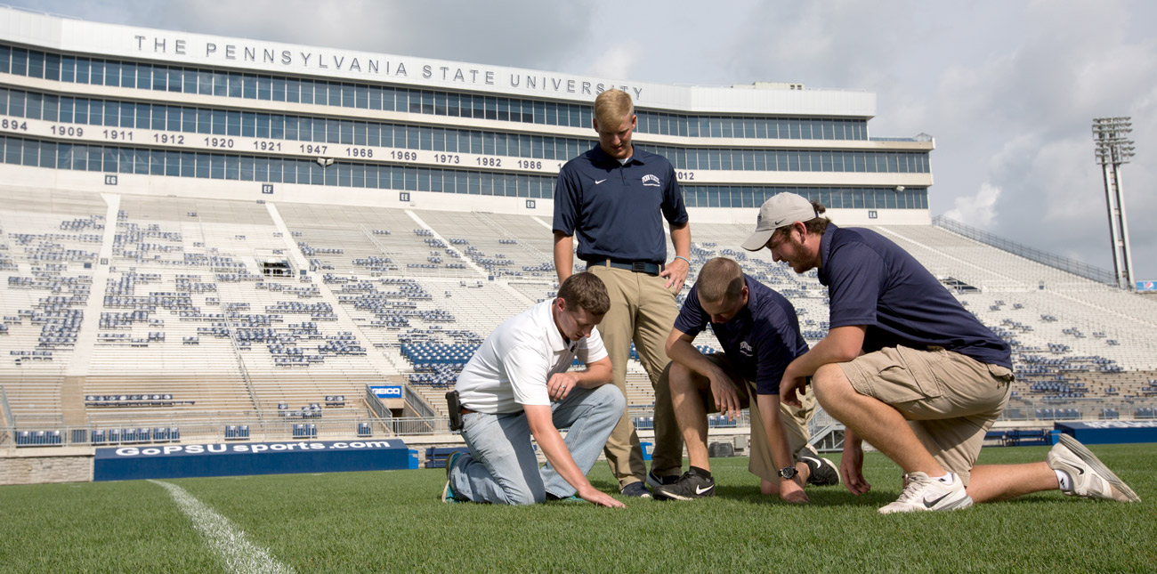Three students and an instructor examining the turf in Beaver Stadium
