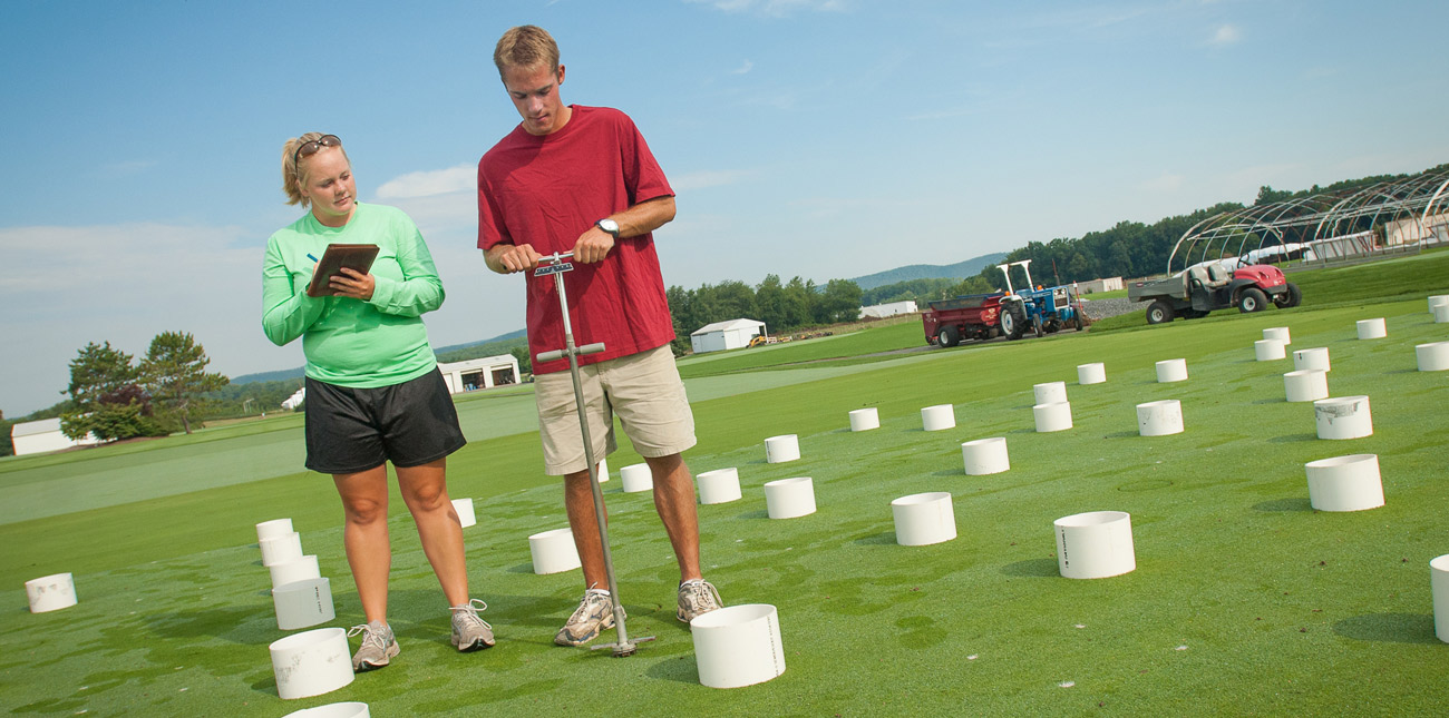 Two students taking core samples in a turf field