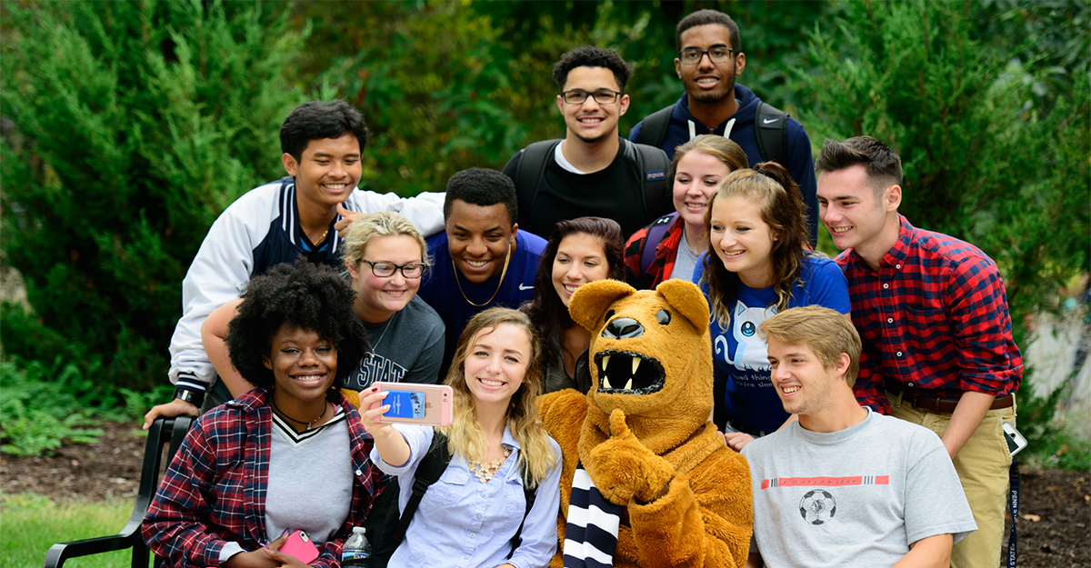 Large group of students sitting on bench taking a selfie with the Nittany Lion